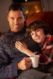 Vater und Sohn, die mit dem heißen Getränk fernsieht sich entspannt Lizenzfreies Stockbild