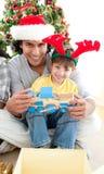 Vater und Sohn, die mit einem Weihnachtsgeschenk spielen Lizenzfreies Stockbild