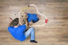 Vater und Sohn, die mit Zug spielen Stockfotografie
