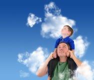 Vater und Sohn, die oben im Wolken-Himmel schauen Stockfotografie