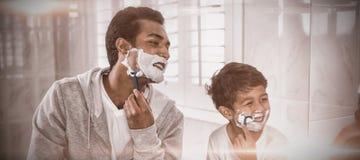 Vater und Sohn, die sich zusammen rasieren stockbilder