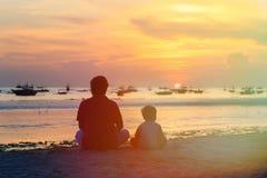 Vater und Sohn, die Sonnenuntergang auf Strand betrachten Stockbilder