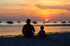 Vater und Sohn, die Sonnenuntergang betrachten Lizenzfreies Stockfoto
