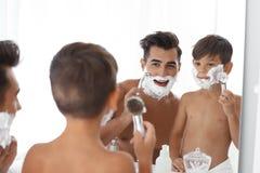 Vater und Sohn, die Spaß beim Rasieren haben stockfotos