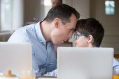 Vater und Sohn, die Spaß habend aufeinander einwirkt, wenn Computer gespielt werden lizenzfreie stockbilder