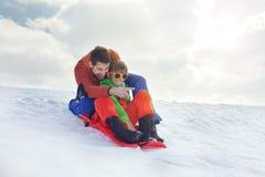 Vater und Sohn, die Spaß im Schnee, schiebend hat Lizenzfreies Stockbild