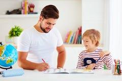 Vater und Sohn, die Spaß zusammen am Schreibtisch, das Buch färbend hat stockfotos