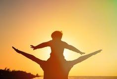 Vater und Sohn, die Spaß auf Sonnenuntergang haben Stockfotografie