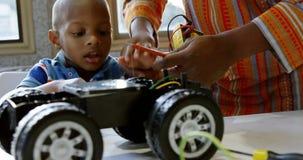 Vater und Sohn, die Spielzeugauto in einem behaglichen Haus 4k reparieren stock footage