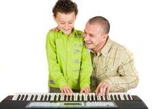 Vater und Sohn, die versuchen, Klavier zu spielen lizenzfreies stockbild