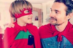 Vater und Sohn, die vortäuschen, Superheld im Wohnzimmer zu sein Lizenzfreie Stockfotos