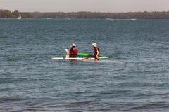 Vater und Sohn, die Windsurfenreparaturen im Wasser durchführen, um schneller zu gehen Verpf?ndung ?ber einem Wassersportwettbewe lizenzfreie stockfotografie