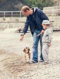 Vater und Sohn, die wirh kleinen Welpen auf der Küste spielen Stockfoto