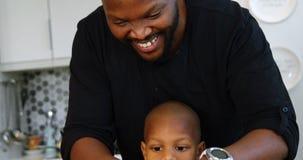 Vater und Sohn, die zu Hause Gemüse in der Küche 4k hacken stock footage