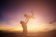 Vater und Sohn, die zur Sonnenuntergangzeit spielen Konzept freundlichen f stockfotografie
