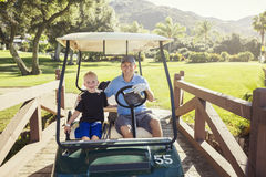 Vater und Sohn, die zusammen an einem Sommertag Golf spielen Stockfoto