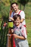 Vater und Sohn, die zusammen einen Zaun malen Stockfoto