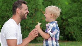 Vater und Sohn, die zusammen Eiscreme essen stock footage