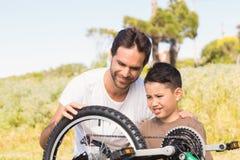 Vater und Sohn, die zusammen Fahrrad reparieren Lizenzfreie Stockfotografie