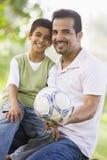 Vater und Sohn, die zusammen Fußball spielen Lizenzfreie Stockfotografie