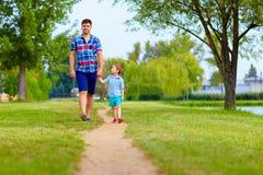 Vater und Sohn, die zusammen in Park gehen stockfoto