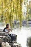 Vater und Sohn, die zusammen am See fischen Stockbilder