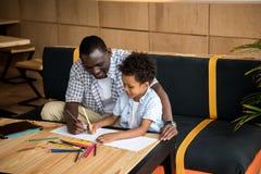 Vater und Sohn, die zusammen zeichnen Stockbilder