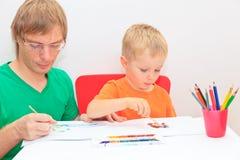 Vater und Sohn, die zusammen zeichnen Stockbild