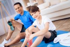 Vater und Sohn haben einen Rest, nachdem sie trainiert haben stockfoto