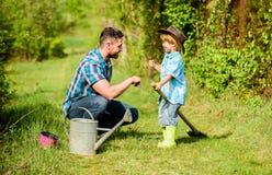 Vater und Sohn im Cowboyhut auf Ranch Eco-Bauernhof kleiner Jungenkinderhilfsvater bei der Landwirtschaft Gie?kanne, Topf und Sch lizenzfreies stockfoto