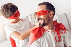 Vater und Sohn im helfenden Mann des Jungen superheroe Kostüme zu Hause, zum der netten Nahaufnahme der Maske zu binden stockfotografie
