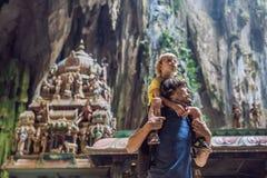 Vater und Sohn im Hintergrund von Batu-Höhlen, nahe Kuala Lumpu stockbild