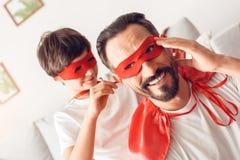 Vater und Sohn im Jungen superheroe Kostüme zu Hause, der Maske an lächelnder Nahaufnahme des Vatis binden hilft lizenzfreies stockfoto