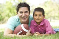 Vater und Sohn im Park mit amerikanischem Fußball Stockfotos