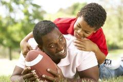 Vater und Sohn im Park mit amerikanischem Fußball lizenzfreie stockfotografie