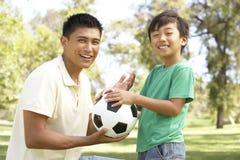 Vater und Sohn im Park mit Fußball stockbild