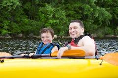 Vater und Sohn kayaking sind lizenzfreie stockbilder