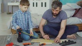 Vater und Sohn messen Stück Holz mit der Maßspule, die fertig wird, etwas zusammen zu konstruieren Innerehaus stock video