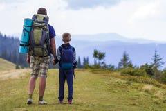 Vater und Sohn mit den Rucksäcken, die zusammen in den szenischen Sommergrünbergen wandern Vati und Kind, die Landschaftsberg gen lizenzfreie stockfotografie