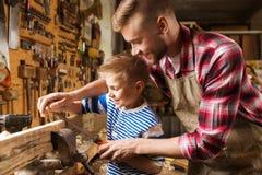 Vater und Sohn mit der Raspel, die an der Werkstatt arbeitet lizenzfreie stockfotos