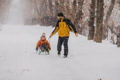Vater und Sohn mit einem Schlitten im Freien im Schnee Stockfoto