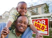Vater und Sohn mit Grundbesitz-Zeichen und Haus Lizenzfreies Stockfoto