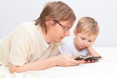 Vater und Sohn mit Handys zu Hause Lizenzfreies Stockbild