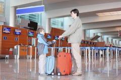 Vater und Sohn mit Koffer in der Flughafenhalle Stockbild