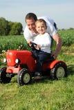 Vater und Sohn mit rotem Traktor Stockfotografie