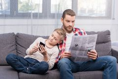 Vater und Sohn mit Zeitung und Smartphone Stockfotografie