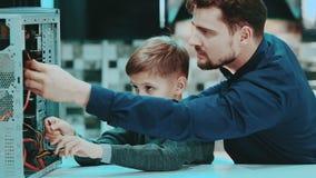 Vater und Sohn reparieren einen Computer stock footage