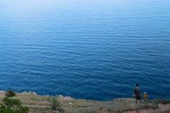 Vater und Sohn stehen auf dem Ufer und betrachten das Meer Stockfotos