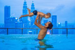 Vater und Sohn Swimmingpool im im Freien mit Stadtansicht in blauen Himmel lizenzfreie stockbilder