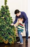 Vater und Sohn verzieren den Weihnachtsbaum lizenzfreie stockbilder
